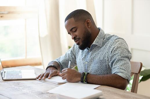 focused-african-man-student-freelancer-making-notes-studying-with-picture-id1170519330